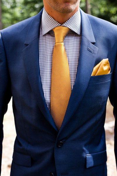 cravatta oro abbinata a un abito blu