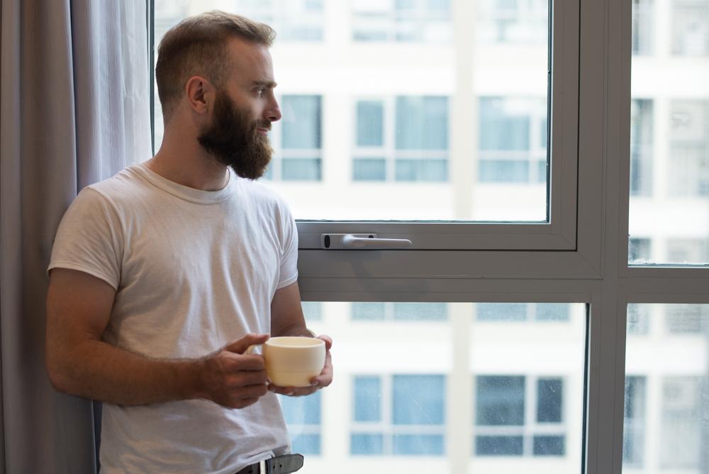 uomo che guarda dalla finestra