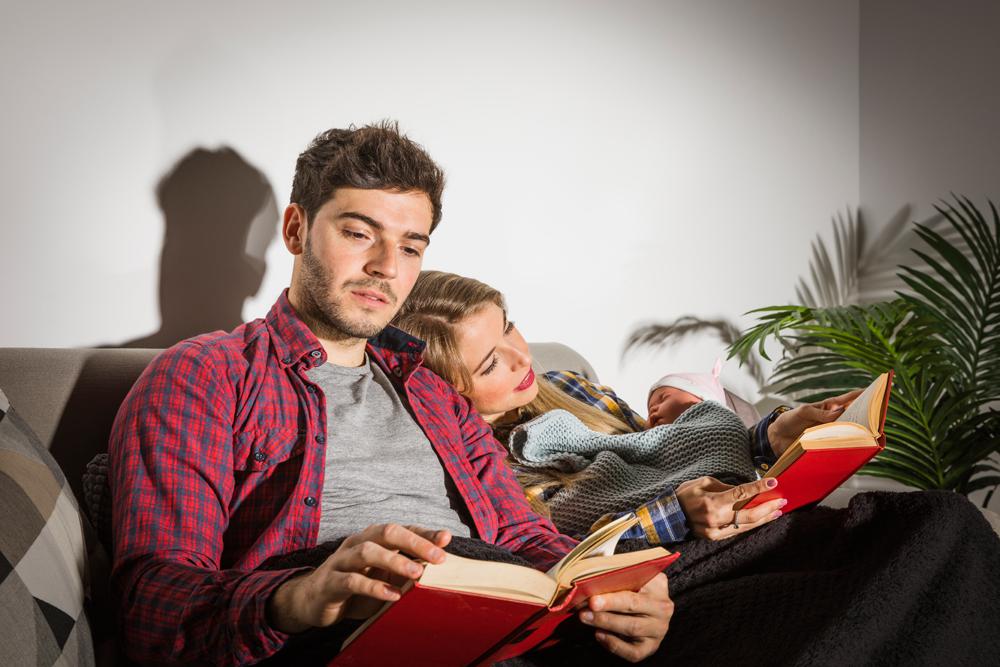 marito moglie e figlio in casa che leggono