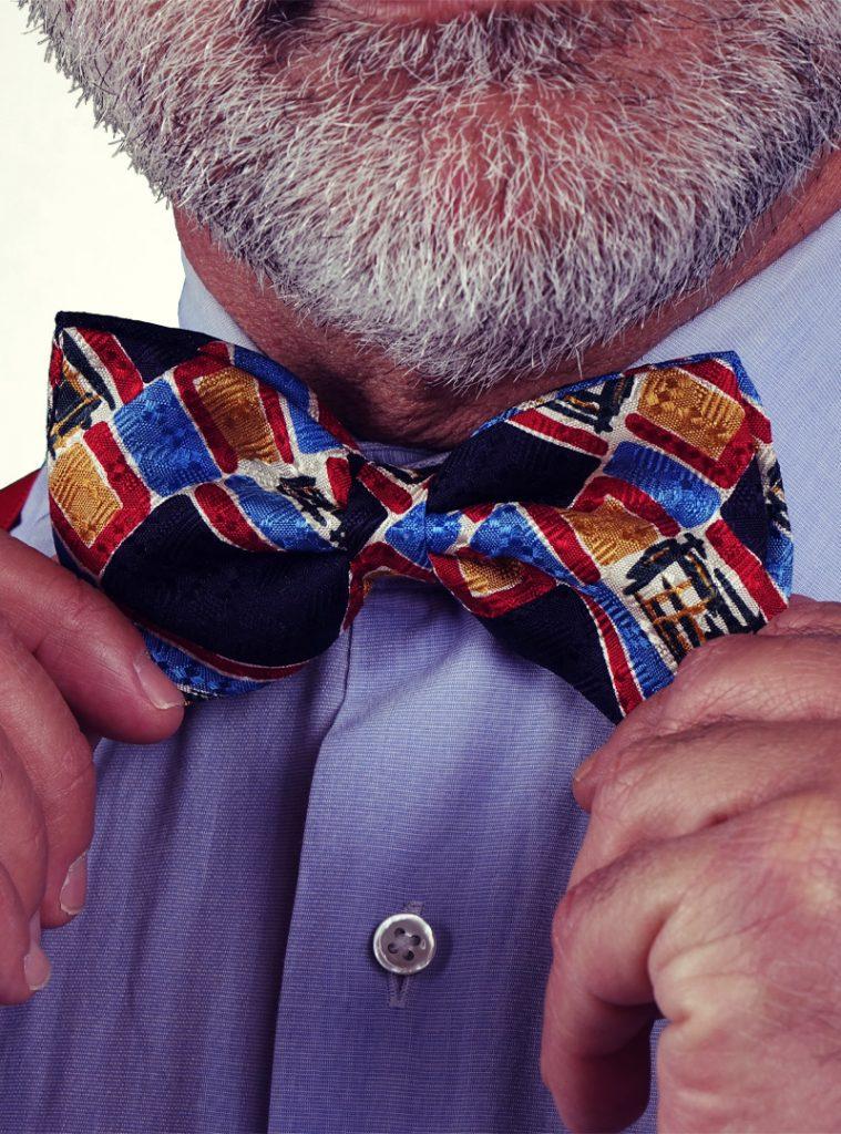 Particolare di una cravatta a farfalla vintage indossata con bretelle in elastico rosse.